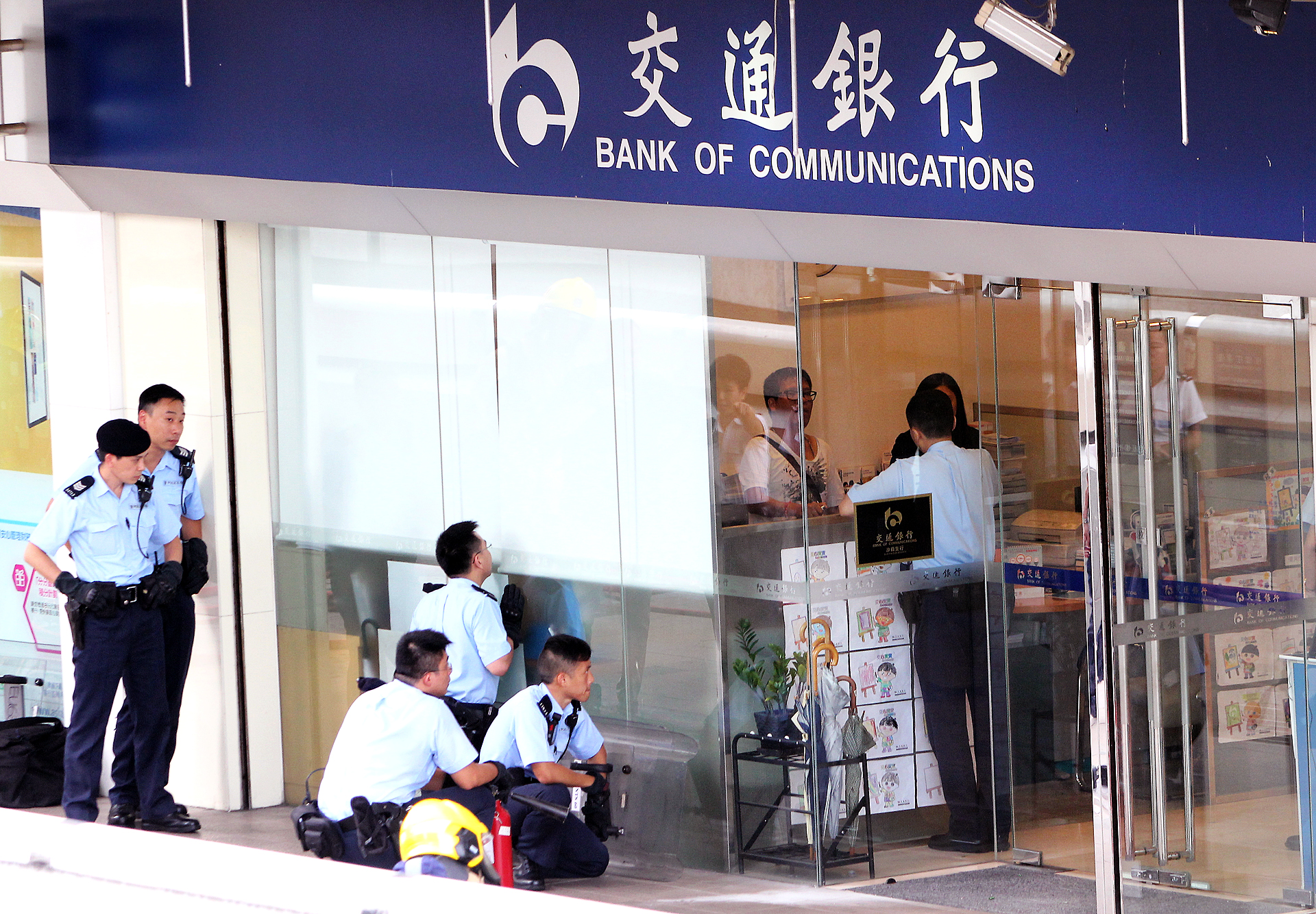 Policemen and firemen standing by outside where the suspect was said to have taken bottles of a flammable liquid into a branch of the Bank of Communications at Lucky Plaza in Sha Tin. The man was later seen being led away by the police. 18JUN15